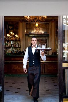 Example of Waiter at a fine dining wedding, plated service. Somehow has apron pants. French Cafe, French Bistro, Restaurant Uniforms, Cafe Restaurant, Kellner Uniform, Waiter Uniform, Hotel Uniform, Staff Uniforms, Pizzeria