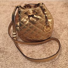 """Michael Kors Jules Drawstring Crossbody Pale Gold. Thus says the bag - Glam! Glamour!! Glamorous!!! with Quilted embossed leather, Gold-tone Hardware, Cross-body for convenience - It's a must have.! It has 3 card slots and measures 6""""W x 6-1/2""""H x 3"""" D. This bag has never been worn, however it has a very small (tiny) paper cut on the back....see 3rd picture - hardly noticeable. Therefore, I have discounted the price of the bag to reflect this! Michael Kors Bags Crossbody Bags"""