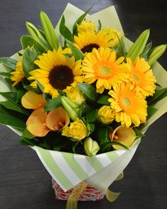 Summer Sunshine Bouquet in a vox. With sunflowers, gerberas, lilies, calla lilies & roses.