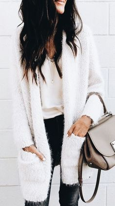 Cozy white cardigan over white blouse and black jeans.