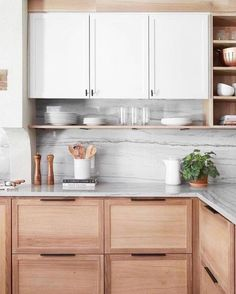 white marble backsplash and natural wood cabinets