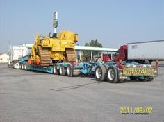 CAT pipe later minus the boom and ROPS, on a triaxle RGN and 2 axle stinger, with triaxle power unit.