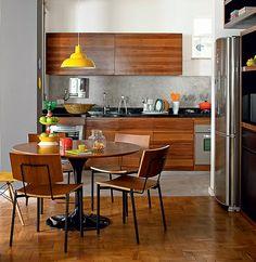 A cozinha de 15 m² era ampla, mas a moradora sentia falta de um espaço para receber os amigos. Com o projeto do escritório FMB Arquitetos, a área de preparo de comida foi reduzida e um novo ambiente com mesa redonda para cinco pessoas surgiu