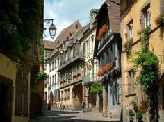 Riquewihr: Sloping narrow paved street lined with houses, colourful facades and windows decorated with geranium flowers - France-Voyage.com
