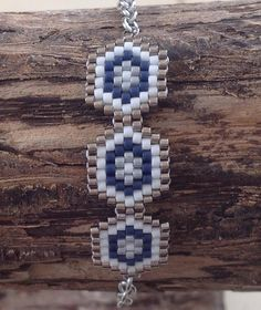 Bracelet en perles MIYUKI 11 délicas blanc, argent et marine Tissage à la main avec une aiguille Dimensions hors accroche : 4,2 x 1,22 cm Fermoir mousqueton et chaîne acier inox Longueur : 16,5 cm Vous pouvez lavoir dans la longueur que vous désirez , il suffit de me le préciser Peyote Beading, Woven Bracelets, Brick Stitch, Bead Weaving, Beading Patterns, Herringbone, Projects To Try, Creations, Bracelets