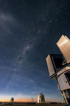 June 10,2014:Sun begins to rise over Very Large Telescope at ESO's Paranal Observatory in Chile.One of VLT's Unit Telescopes at bottom right,illuminated by moonlight.In distance 2 Auxiliary Telescopes point to sky.VLT consists of 4 8.2-meter Unit Telescopes, 4 movable 1.8-meter Auxiliary Telescopes.Nicolas Blind, astronomer who visited Paranal Observatory for few days December 2012,took photo.