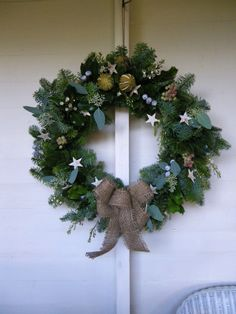 grey and green foliages and berries, bark stars and a natural hessian bow, by petal and twig