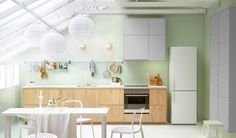 Open, bright kitchen space with IKEA cabinets, dining table and chairs.