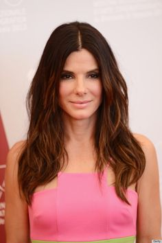 sandra bullock Va-va-voom! Bullock is serving '70s glam with her sultry, smokey eyes, center-parted waves and pale pink lipstick. Her rich hair color warms up her complexion and balances out her neon pink dress.