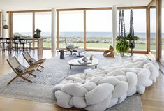 Kelly Behun's beachside Long Island, New York home is furnished with organic textures — woven textiles, hand-made ceramics and potted trees — that contrast with the residence's clean-lined contemporary architecture. The antique Samarkand rug is from Doris Leslie Blau, the Boa sofa is by the Campana Brothers and Behun designed the macrame plant holders.
