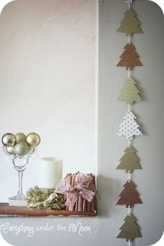 Midwestern Girl: Christmas Tree Garland with Nikki from Everything Under the Moon: trace tree template on holiday cardstock paper; hole-punch on top & bottom and sting on yarn & use a dot of hot glue.