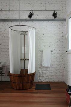 baño, bañera exenta de madera, cortinas, paredes de ladrillo pintadas de blanco y suelo de parquet
