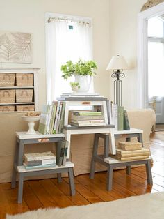"""From Better Homes and Gardens:  """"Use neutrals to unify and elevate unlikely items into sophisticated furnishings. Practical and affordable wooden step stools, painted in a chic palette of gray and white, are transformed into a makeshift library that complements the ivory walls, distressed white cabinetry, and beige fabrics and woven materials in this warm and inviting living room."""""""