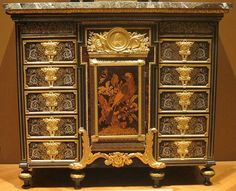 A cabinet (c.1690) with 10 drawers detailed with pattern and ebony, metal  tortoiseshell and gilded bronze , figures of painted and gilded oak . And marble top . This cabinet is now at Cleveland Museum of Art