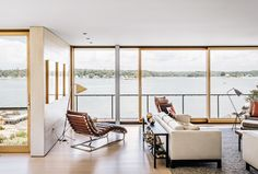 The operable windows and doors throughout are by Bayerwald | Modern Connecticut summer home renovation with Desiron sofa and Restoration Hardware chaise lounge in the living room