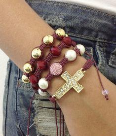 D3000 <br> <br>Kit de pulseiras shambalas, confeccionadas em macram� com cord�o encerado na cor bordeaux, composto de 4 pulseiras: <br>- 1 pulseira de crucifixo dourado e strass <br>- 1 pulseira de p�rolas de 12 mm, contendo uma bola de strass <br>- 1 pulseira de cristais facetados de 12 mm na cor vermelho <br>- 1 pulseira de p�rolas douradas <br> <br>> Pode ser confeccionado em outras cores de cord�o encerado (cores dispon�veis: Amarelo, amarelo c�trico, azul claro, bege claro, bege escuro…