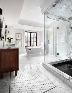Contemporary bath features a corner shower accented with seamless glass walls and filled with marble surround as well as black tiled shower floor across from stained double washstand topped with whit marble paired with rectangular, pivot mirrors atop marble floor adorned with marble basketweave tiles with black border.