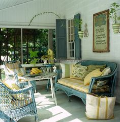 A comfortably furnished porch with a wicker sofa and armchairs complete with scatter cushions