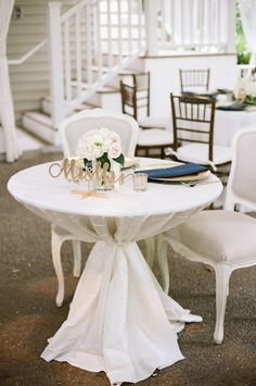 Ivory Pintuck Linen with navy blue accents make a beautiful sweetheart table for the bride and groom.   CJs Off the Square,  Franklin, Nashville, TN Navy and Gold Spring Garden Wedding,  Jenna Henderson Photography #mr.andmrs. #sweethearttable