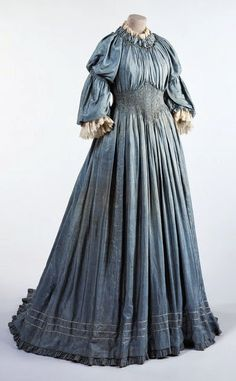 Dress of plain weave blue pongee silk trimmed with smocking and machine-made lace. Full length with train, medium height round neck, double-puff elbow length sleeves, trimmed with smocking and frilled edge. - Liberty Co. 1890s Fashion, Edwardian Fashion, Vintage Fashion, Paris Fashion, Vintage Outfits, Vintage Dresses, Blue Dresses, Historical Costume, Historical Clothing
