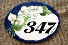 Placa Oval Copo de Leite Clay Tiles, Ceramic Clay, Ceramic Painting, House Numbers, Beach Cottages, Decoupage, Number Plates, Decorative Plates, Carving