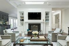 Beautiful living room features a skylight over a board and batten wall lined with a white fireplace mantle with black surround and a niche filled with a flatscreen TV flanked by built-in shelving.