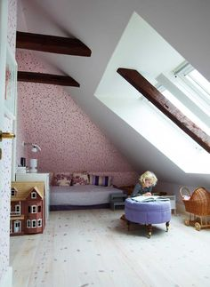 Cute and girly kids room with a delicate rose wallpaper. The sloping walls together with the high ceiling gives the felling of a small den.
