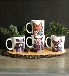 "Let these forest friends warm up your winter season. Perfect for creating cozy cabin style, our ceramic Woodland Animal Mug Set features an owl, a deer, a raccoon and a fox—critters you'll find in the great North Woods. A great gift for anyone who loves rustic style and lodge living. Set of four. Each mug is 4""H"