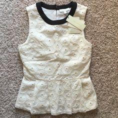 Off White Peplum Top Large eyelet off white peplum top with black trim around the neck. New with tags, never worn! Fit is in between small and extra small. Back keyhole button fasten. Comes with an extra button in one of the tags. Side Zipper. MM Couture Tops Blouses