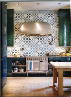 Stunning kitchen with emerald green lacquered cabinets with open cabinets framing the footed ...