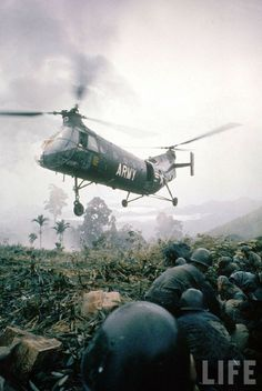 American Piasecki H-21 helicopter hovering above soldiers in combat zone during the Vietnam War, c.1962.