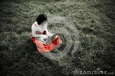 Female using a laptop whilst sitting on the grass, vintage black and white look with red colour standing out. Textured, with soft focus, glow and overexposure intentionally for effect.