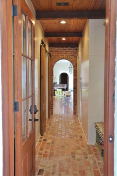 back hall entry gallery, brick floors, antique beams and wood ceiling, antique cypress doors, wood walls, Rich in textures.