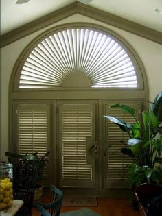Power remote control arched shutter and door shutter panels one with a cutout for lever handle all in custom color by Budget Blinds of Lewes, DE.