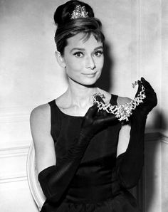 "Audrey Hepburn dressed as Holly Golightly, doing a publicity shot for ""Breakfast at Tiffany's.""  She has the rhinestone pin or tiara in her hair, but in her hands she's holding a large diamond choker necklace, set in the center with the Tiffany Diamond -- over 120 carats of canary diamond.  (The necklace, at a guess, was designed by Jean Schlumberger; it has the style that I recall as his signature.)"