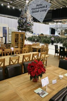 Oak bar stools, oak dining chairs and matching dining tables on display at Earls Court, London.  Christmas festive interiors exhibition attracting a large numbers of interior designers, home decor type people and businesses from around the world.