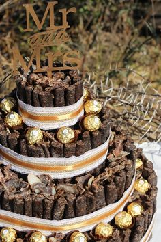 This wedding biltong cake has accents of gold and hessian made with 3 tiers for guest to enjoy. The biltong and droewors cake is custom made for a safari wedding with the addition of Ferrero Rocher chocolates to compliment the theme of the wedding and it adds a beautiful touch to the desert/snack table. MK Biltong Imagineer can custom design and make a biltong cake for you in any colour and size for your special occasion. Themed Wedding Cakes, Themed Cakes, Wedding Ideas South Africa, 30th Birthday Cakes For Men, Safari Wedding, Bush Wedding, Traditional Wedding Decor, Biltong, Country Style Wedding
