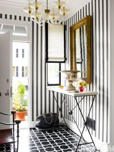 In the foyer of a Georgetown townhouse designed by Hillary Thomas and Jeff Lincoln, the black and white of Montgomery 1 marble floor tiles by Ann Sacks and Block Print Stripe wallpaper by Farrow & Ball is reminiscent of Dorothy Draper.