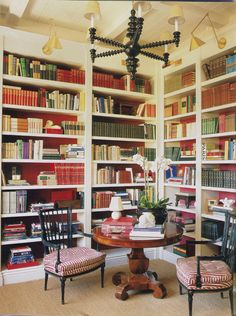 he library in the entryway of a Hollywood Hill house. The bookcases, running nearly to the high ceiling, are painted white with red-painted walls behind to add color to the space. A small pedestal table and pair of arm chairs provide a place for browsing and stacking new purchases. A well-designed space.