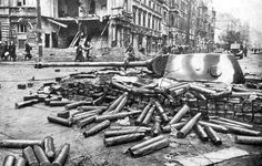Battle of Berlin, May 1945: The battle is over and the German tank emplaced as stationary artillery is surrounded by the spent shells fired at the enemy. The neighborhood is ruined. Civilians increasingly appear. The occupation has begun. At least there is no more shooting.