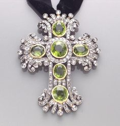 A peridot, diamond and silver-topped gold cruciform pendant