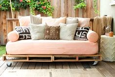 outdoor pallet bed. love the mix of coral and other fabrics. & it's on wheels!