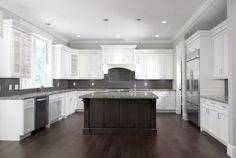 white cabinets grey glass backsplash dark island dark wood floor..The cabinets are just a bit too white for me. I absolutely love it!