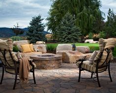 Pavers with the look of natural flagstone are arranged in a circular shape for this rustic fire pit on a patio. The materials are Belgard.