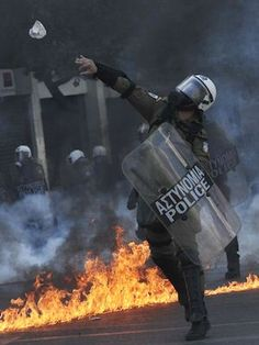 AUSTERITY STRIKES: A police officer throws a stone toward demonstrators during a 24-hours general strike in Athens. Police clashed with youths throwing firebombs on the sidelines of a large protest against new austerity cuts. (AFP)