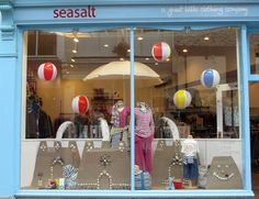 Seaside themed window display with beach balls and sand castles made with hessian by Seasalt window team.