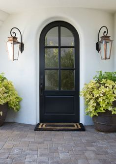 Black & White Modern Farmhouse Meets Classic Tudor Style in Arizona – Hello Lovely Black arched exterior door with lanterns and white house exterior. Black Exterior Doors, White Exterior Houses, Modern Farmhouse Exterior, Modern Farmhouse Style, Interior And Exterior, Arched Front Door, Arched Doors, Entry Doors, Entryway