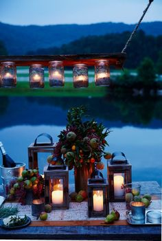 A close up on the Blackberry Farm table overlooking Walland Pond. Mason jar and lantern lighting create an intimate setting for dining.
