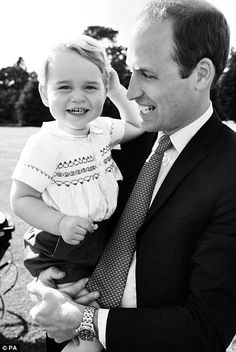 A cheeky Prince George grins as his father cradles him in his arms in this candid black and white shot