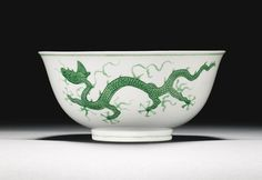 INCISED GREEN-ENAMELLED 'DRAGON' BOWL ZHENGDE MARK AND PERIOD the deep rounded sides rising from a straight foot to a flared rim, decorated to the exterior with two green five-clawed dragons pacing amongst an incised wave ground in pursuit of flaming pearls, the interior with a central medallion enclosing a green dragon writhing amongst clouds, inscribed to the base with a six-character mark within a double-circle 20.2cm., 8in.